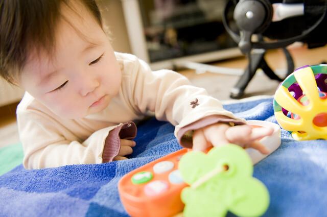 ハイハイしておもちゃを探す赤ちゃん